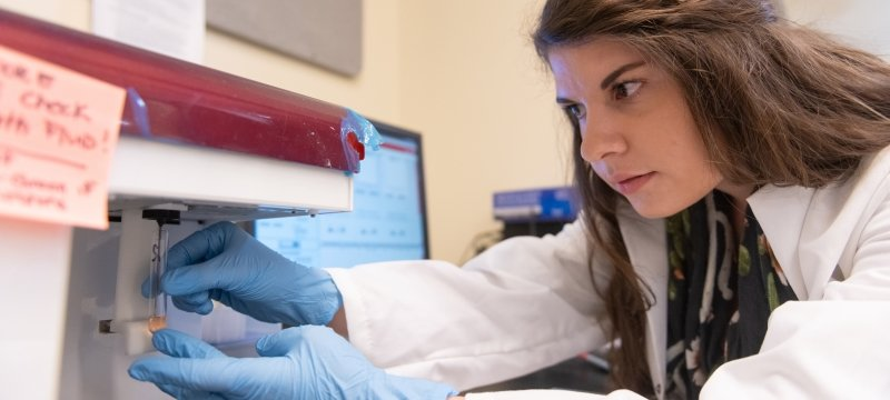 Graduate student inserting a vile into research equipment for analysis.