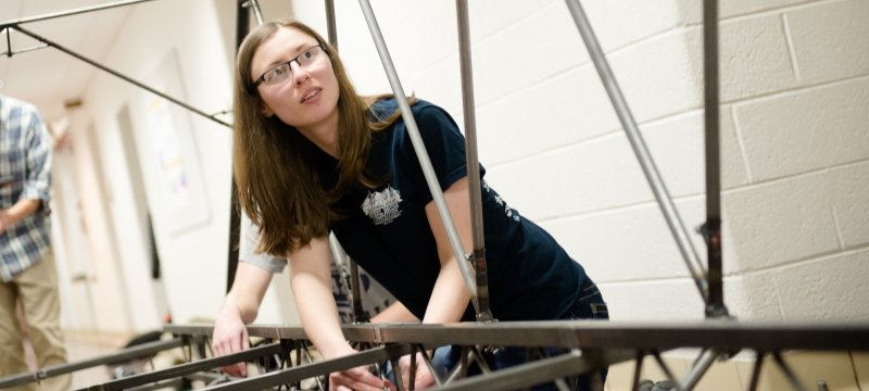 Engineering students working together on a steel bridge.