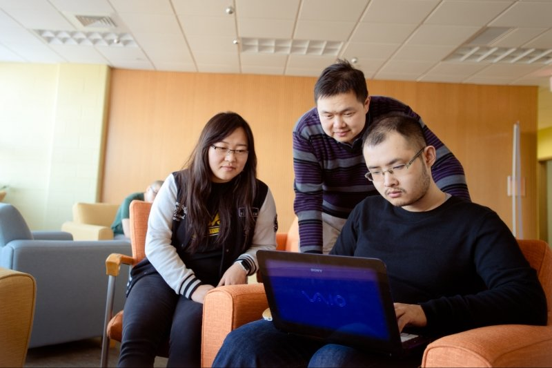 Three international students looking at a laptop.