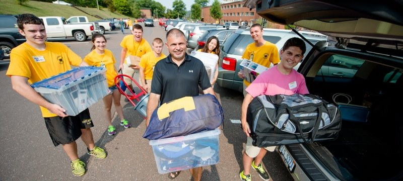 Families help carry items from their cars to their students' residence hall