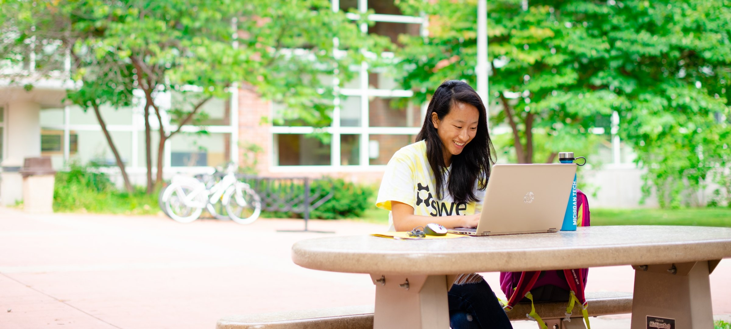 Michigan Tech student studies with a laptop outside on a picnic table.