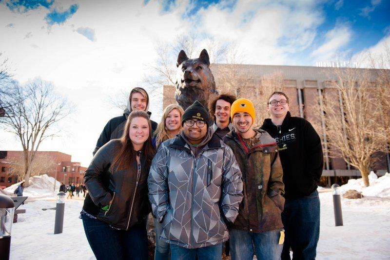 Students standing in frong of the Husky Statue.