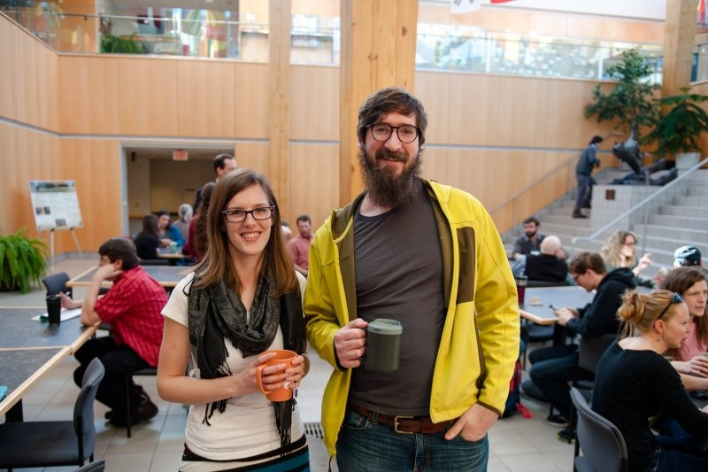 Students smiling with drinks in the Forestry Atrium.