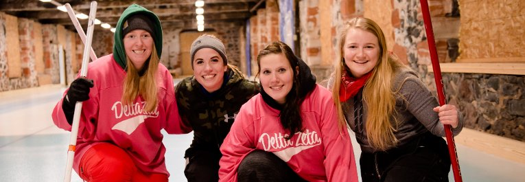 Four Delta Zeta women pose before a game of curling