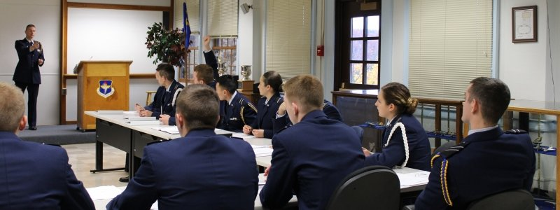 Inside the ROTC building, cadets in uniform at attention in three to four rows