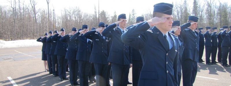 Cadets in uniform standing at attenion, saluting, during a warmer day of a U.P. winter.