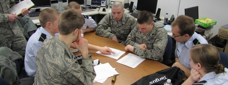 A group of Air Force ROTC and Army ROTC students sitting around a table collaborating on a project