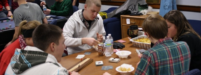 Students sit around a table in the ROTC building in casual dress playing cribbage and eating cake