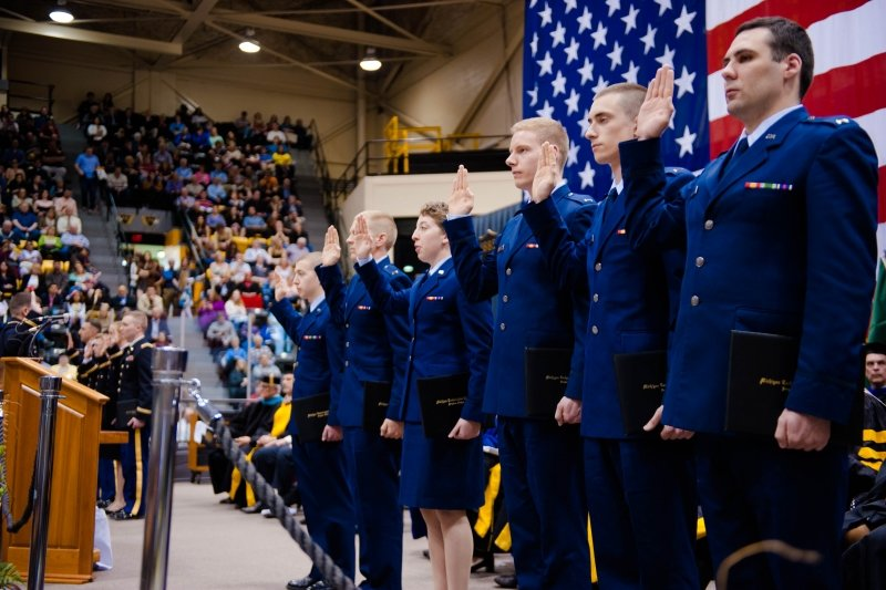 Air Force ROTC Cadets at commencement at attention with their right hands held up for swearing in.