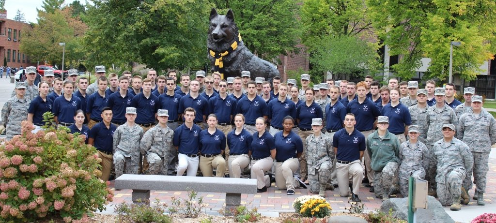 Air Force ROTC students in fatigues with officers in kahkis and polo shirt with AFROTC logo standing in front of the Michigan Tech Husky statue.