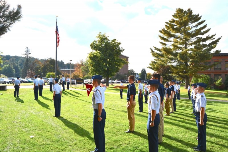 Cadets standing at attention facing the flag outside the ROTC Building