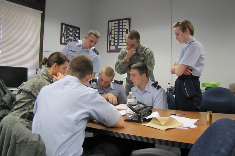 Air Force Cadets and leadership discussing in a group hovering over a report on a table.