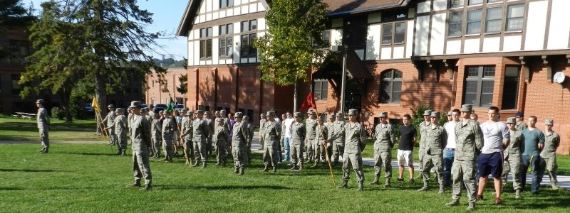Cadets in uniform and high school students in plain clothing standing attention outside the ROTC building