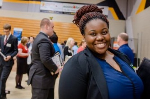 A female student in a business suit smiles during Career Fair.