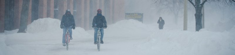 students riding bikes on campus with snowy conditions