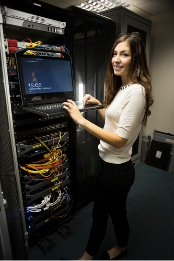 Female student working at a laptop at a server rack.