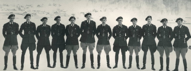 Early 1900s group photo of twelve officers of Engineer Unit of the Reserve Officers Training Corps at the Michigan College of Mining and Technology, the former name of Michigan Tech, standing in a line at attention on the ice of the Keweenaw Waterway in front of Mont Ripley.
