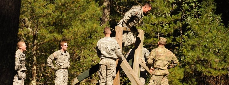 Cadets outside on the Confidence Course, one climbing a wooden structure