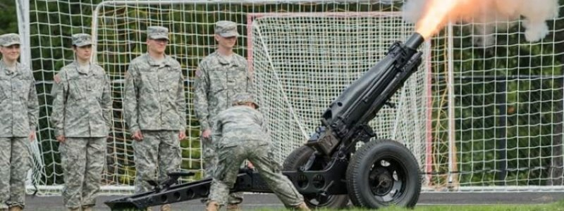 Cadets lined up with one firing the Howitzer cannon