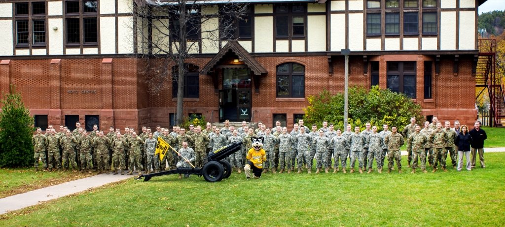 A group image of leadership, students, staff, and Blizzard in formation outside the ROTC building.