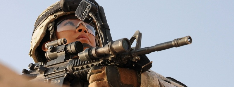 Female office, in full combat gear with riffel pointed, looks into the distance.