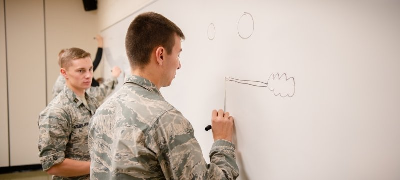 Three students, wearing fatigues, draw a diagram on a whiteboard.