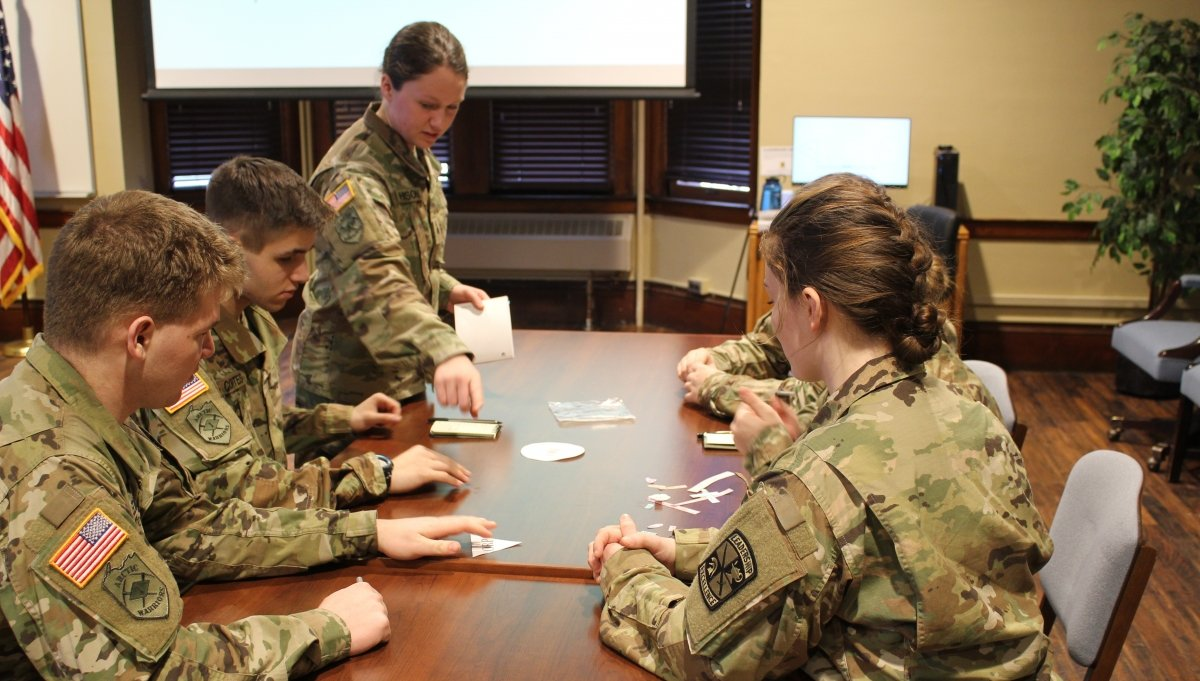 five Students around a table, wearing fatigues, briefing a mission plan.