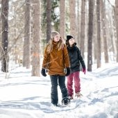 Two students snowshoeing in the woods.