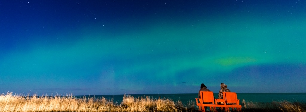 View over Lake Superior at night with Northern Lights in the clouds above; two people are sitting in chairs watching.