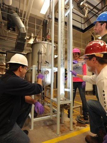 Students work together with hard hats on the floor of a chemical lab