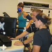 Researchers monitoring results on a computer of a participant running on a treadmill with a mask on.