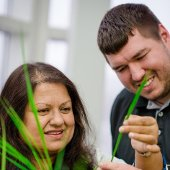 Faculty member showing a plant to a student