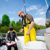 Two researchers on a research vessel taking measurements of the Keweenaw Waterway