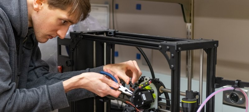 Student working on a 3D printer in a teaching lab.