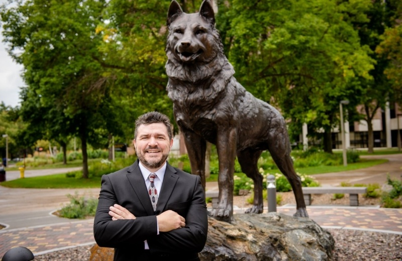Dean Johnson in front of the Husky statue.