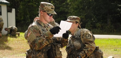 Two ROTC students outside, examining a piece of paper.