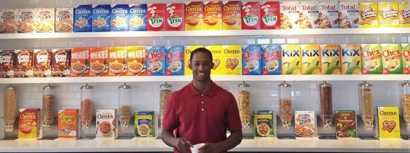 Student Nathan Hood standing in front of shelves of cereal boxes at his internship with General Mills