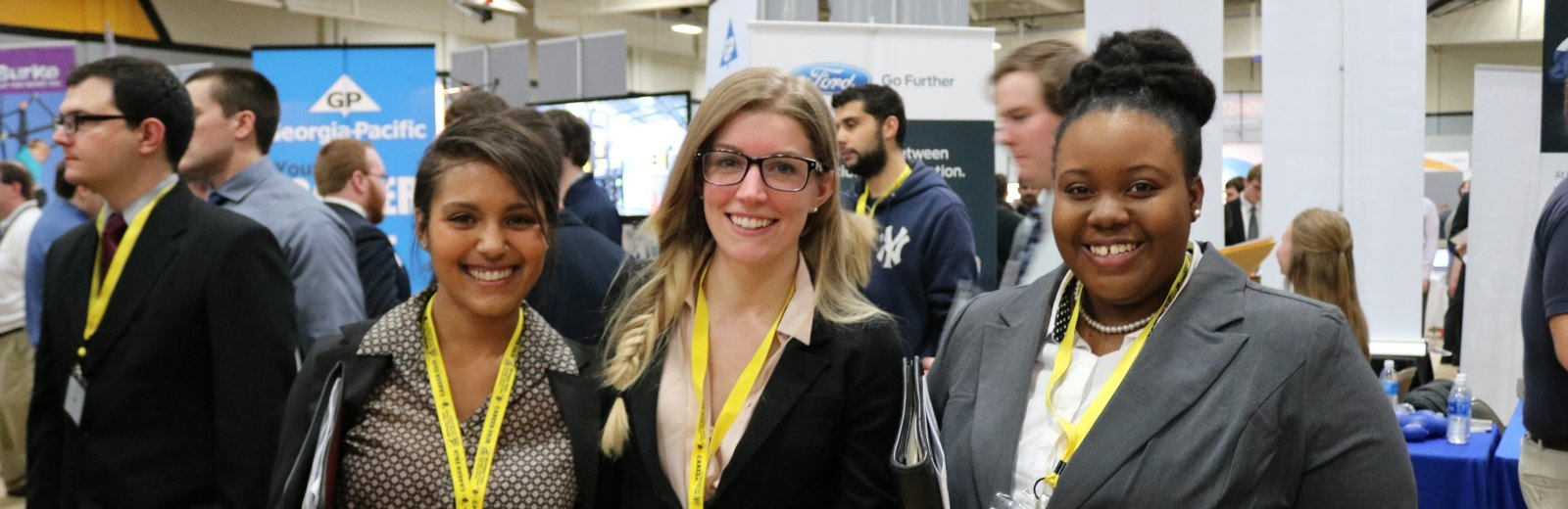 Three smiling students at the career fair