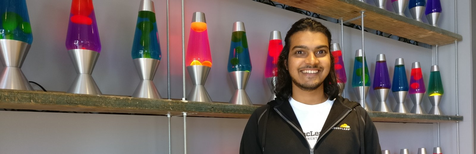 A very happy (smiling) college student stands in front of a shelf full of multi-colored lava lamps.