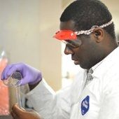 A man pouring chemicals in a lab coat and goggles