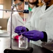 Students in a chemistry lab measuring a liquid in a beaker