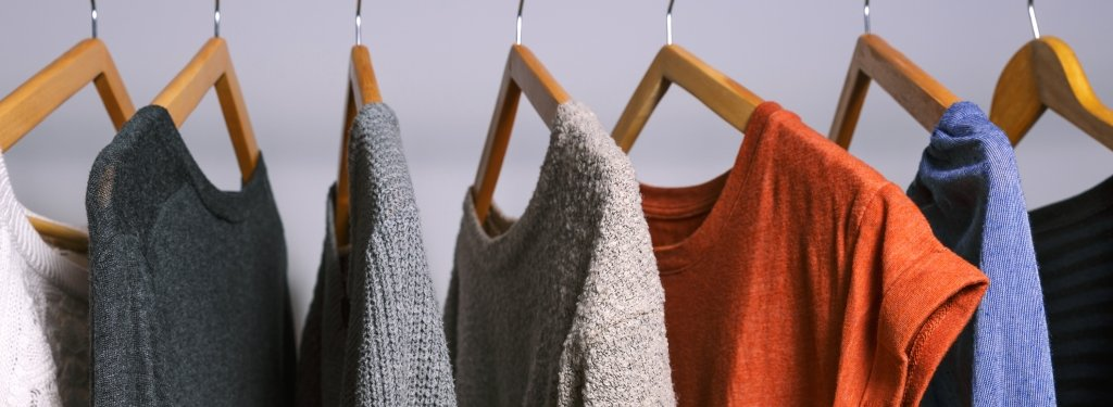 Sweaters and shirts on wooden hangers