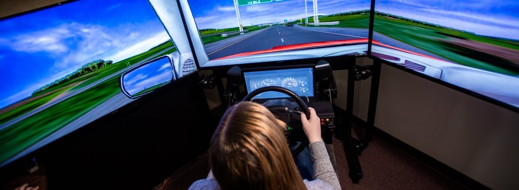 Student participant simulating driving with a wheel looking at a monitor with a display of a road.