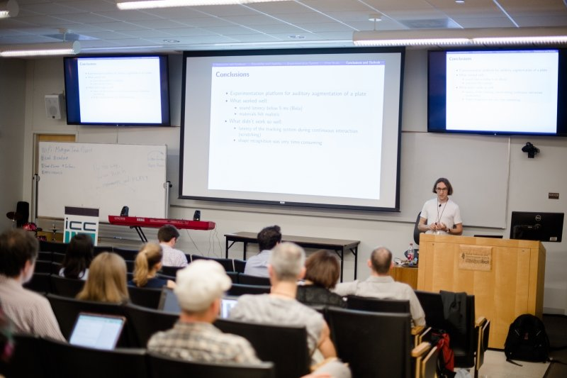 Researcher standing at a podium and giving a presentation