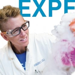 Chemical Kim in a lab coat with safety goggles making colored smoke from a beaker