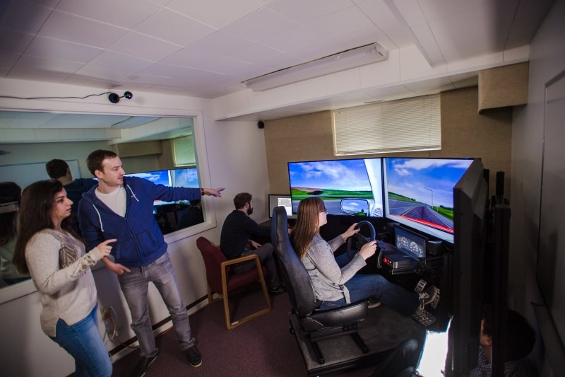 Researchers observing student interacting with driving machine