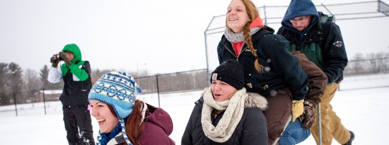 Alumni on a dog sled at the baseball field during Winter Carnival
