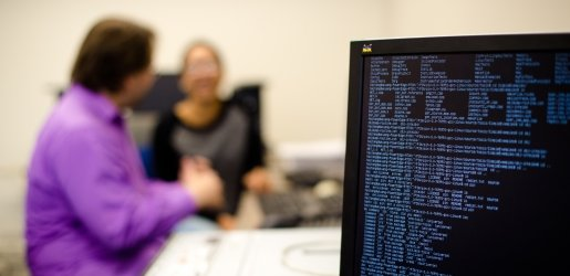 Monitor showing a Linux terminal, while faculty discuss in the background.