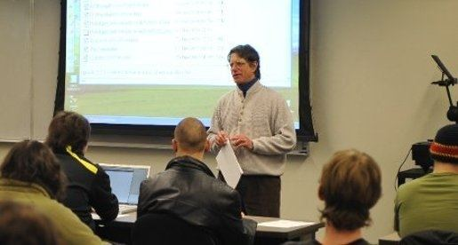 A computer science faculty member lecturing in a classroom.