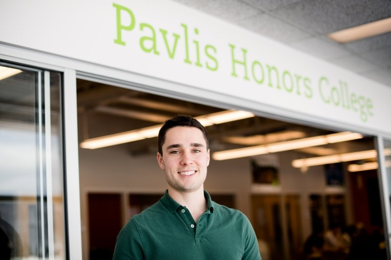 Male student standing in front of the Pavlis Honors College office.